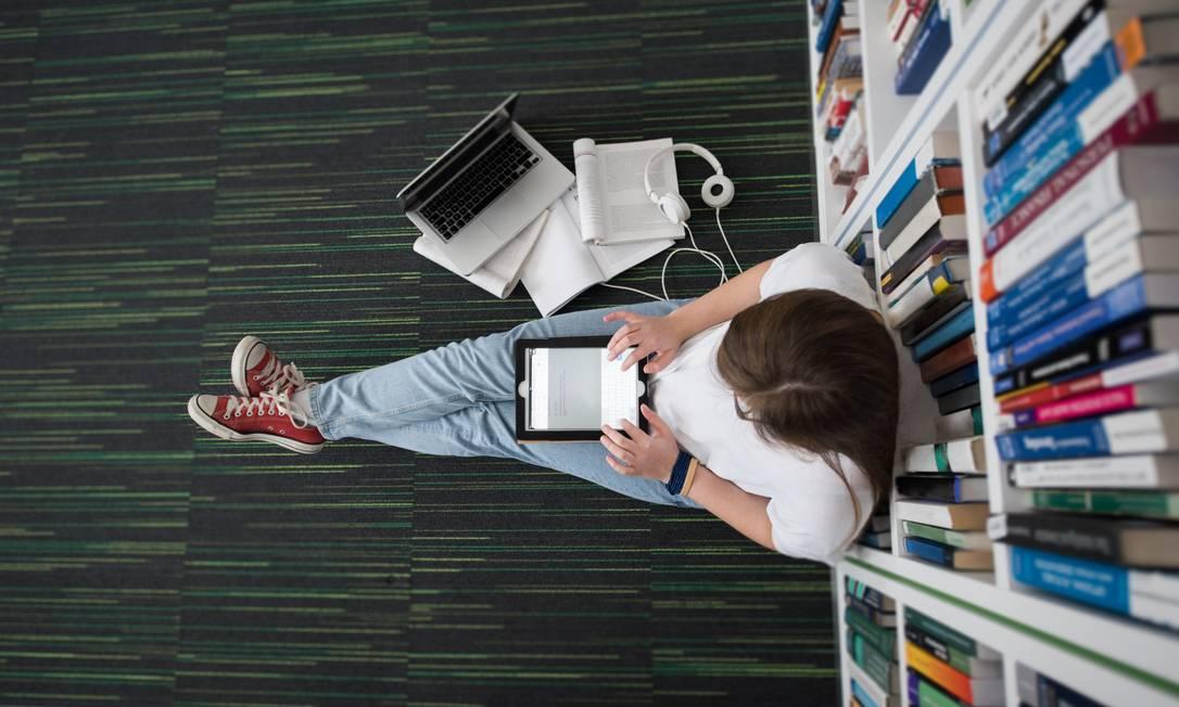 Estudante sentado no chão de biblioteca Foto: Arquivo