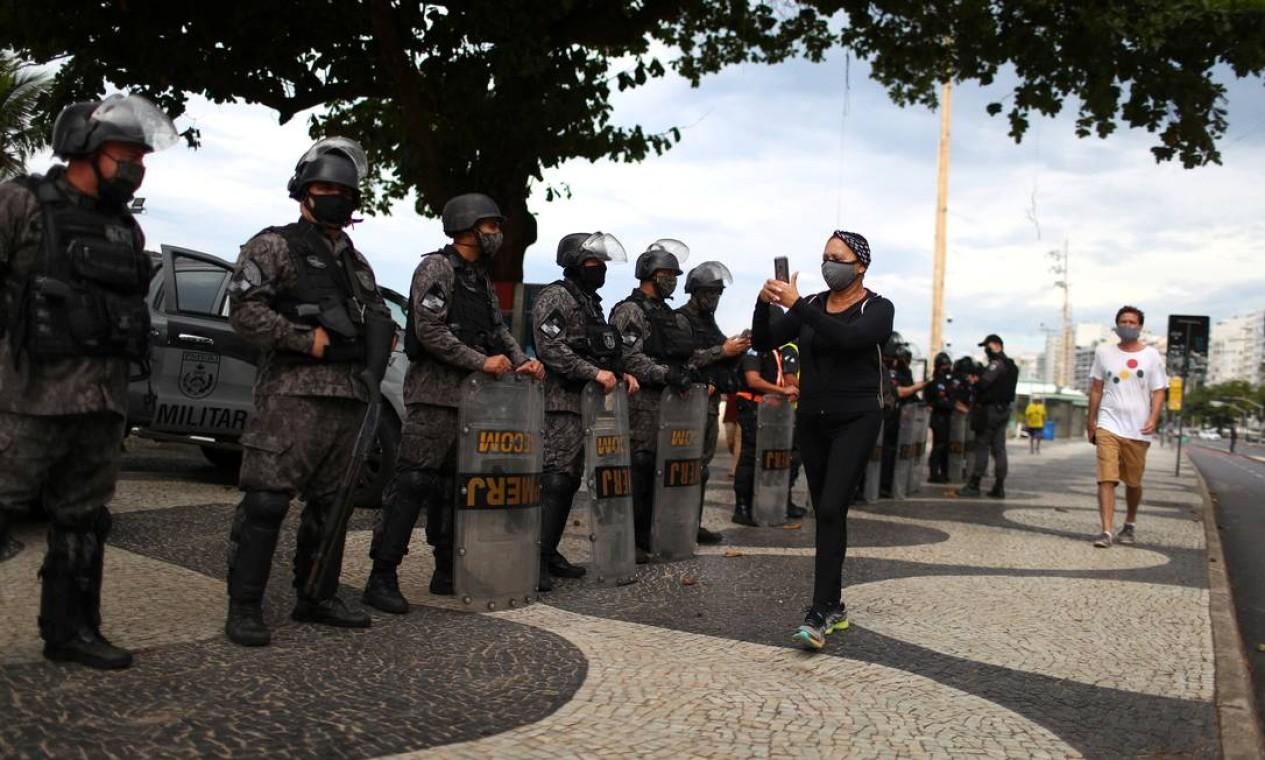 Uma mulher usando uma máscara protetora passa pela polícia de choque durante uma manifestação contra o presidente Jair Bolsonaro e em apoio à democracia na praia de Copacabana, no Rio Foto: PILAR OLIVARES / REUTERS