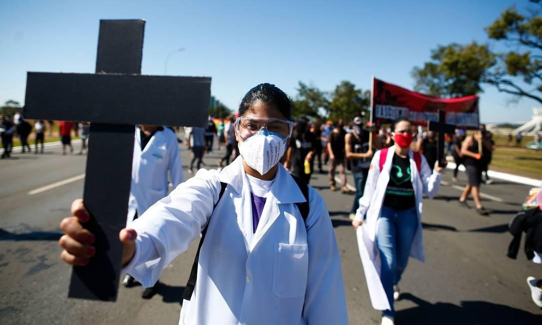 Grupo de enfermeiros carrega cruzes em homenagem aos colegas que morreram no combate à Covid-19, durante o ato em Brasília Foto: SERGIO LIMA / AFP