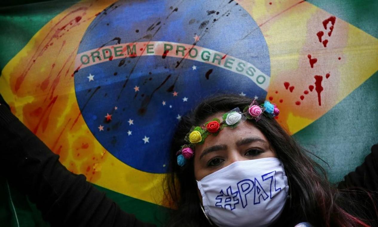 Manifestante segura bandeira do Brasil manchada em protesto contra Bolsonaro, em Porto Alegre Foto: DIEGO VARA / REUTERS