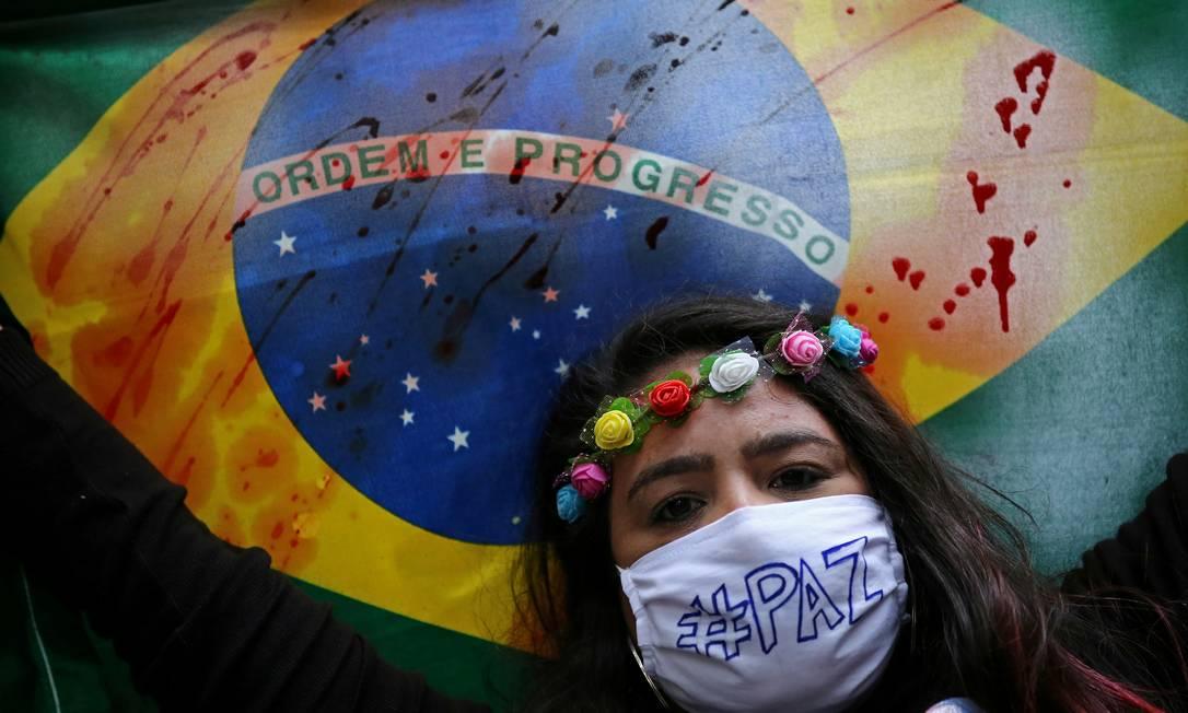 Manifestante segura bandeira do Brasil manchada em protesto contra Bolsonaro, em Porto Alegre Foto: DIEGO VARA/REUTERS / DIEGO VARA/REUTERS