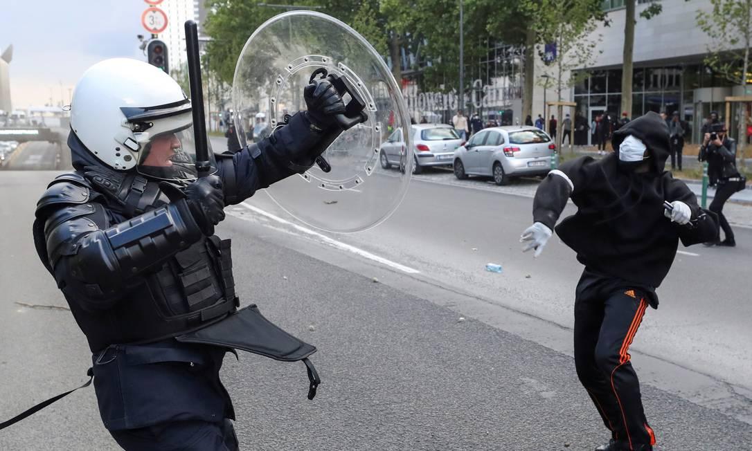 Um manifestante joga um objeto contra um policial durante um protesto, organizado pelo movimento Vidas Negras Importam, contra a desigualdade racial, no centro de Bruxelas, na Bélgica Foto: YVES HERMAN / REUTERS - 7/06/2020