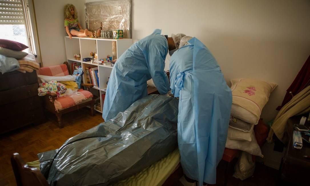 Socorristas do Samu preparam cadáver de um mulher idosa que morreu com suspeita de Covid-19 Foto: Yan Boechat / Agência O Globo