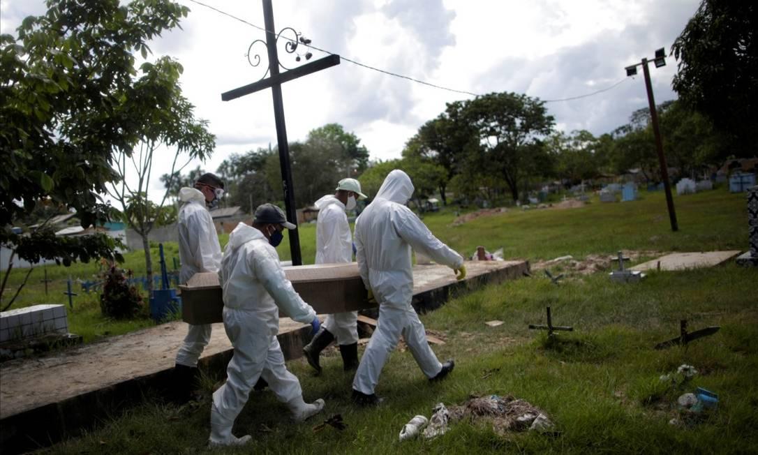Em Breves,na Ilha de Marajó, no Pará, coveiros usam trajes de proteção para realizar o enterro de Manuel Farias, que morreu aos 70 anos Foto: UESLEI MARCELINO / REUTERS / 7-6-2020