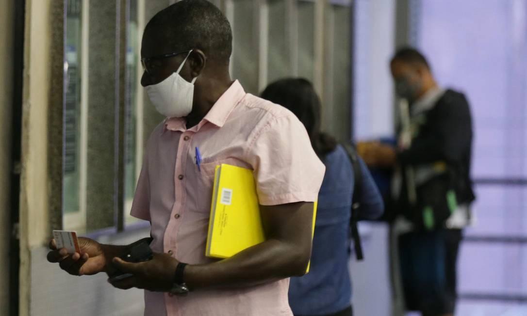 Homem usando máscara compra bilhete de trem sem enfrentar fila no horário que, antes da quarentena, era de pico Foto: Cléber Júnior / Agência O Globo