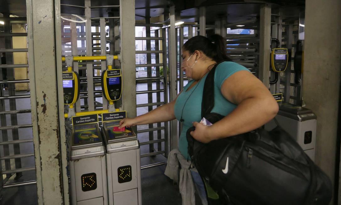Mulher embarca no trem, com cartão pré-pago, sem enfrentar fila na roleta como de costume Foto: Cléber Júnior / Agência O Globo