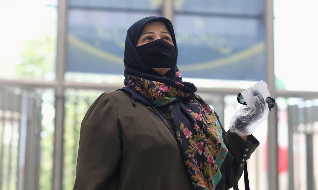 Iraniana usa máscara e luvas em Teerã, capital do Irã Foto: Wana News Agency / VIA REUTERS