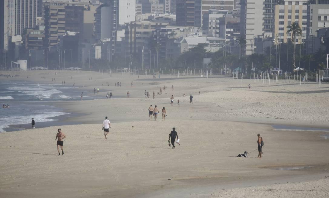 Apesar da suspensão da medidas de flexibilização no Rio, a Praia de Ipanema amanheceu com surfistas na água e pessoas caminhando na areia e no calçadão Foto: Marcia Foletto / Marcia Foletto