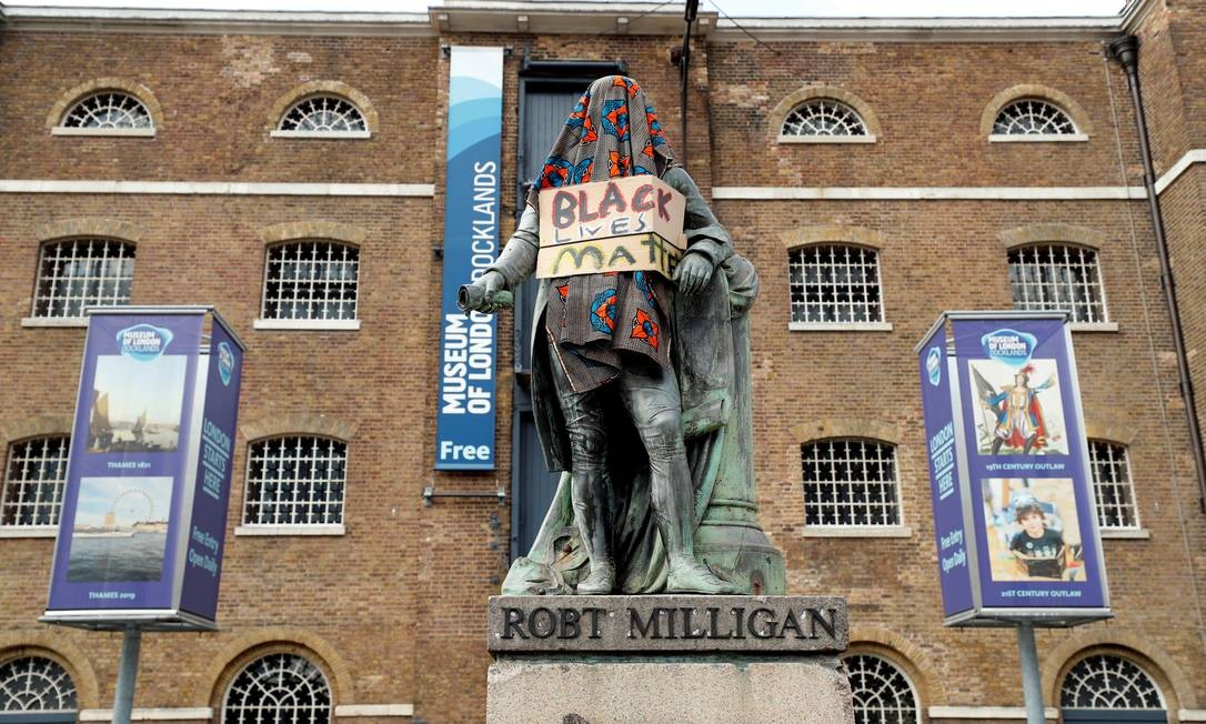 """Estátua de Robert Milligan, um comerciante de escravos do século 18, é vista coberta com um cobertor e um cartaz com mensagem em referência ao movimento """"Vidas negras importam"""", do lado de fora do Museu de London Docklands Foto: JOHN SIBLEY / REUTERS"""