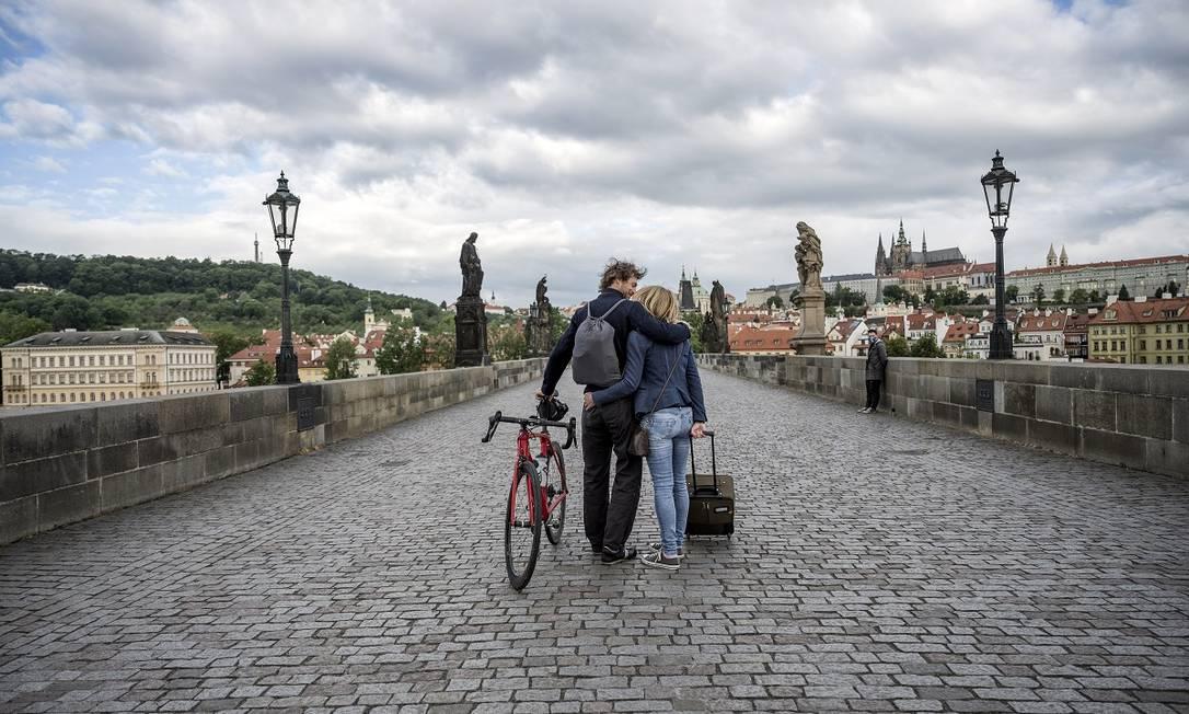 Casal caminha pela Ponte Carlos, que antes da pandemia era um dos lugares mais lotados de turistas em Praga Foto: Laetitia Vancon / The New York Times