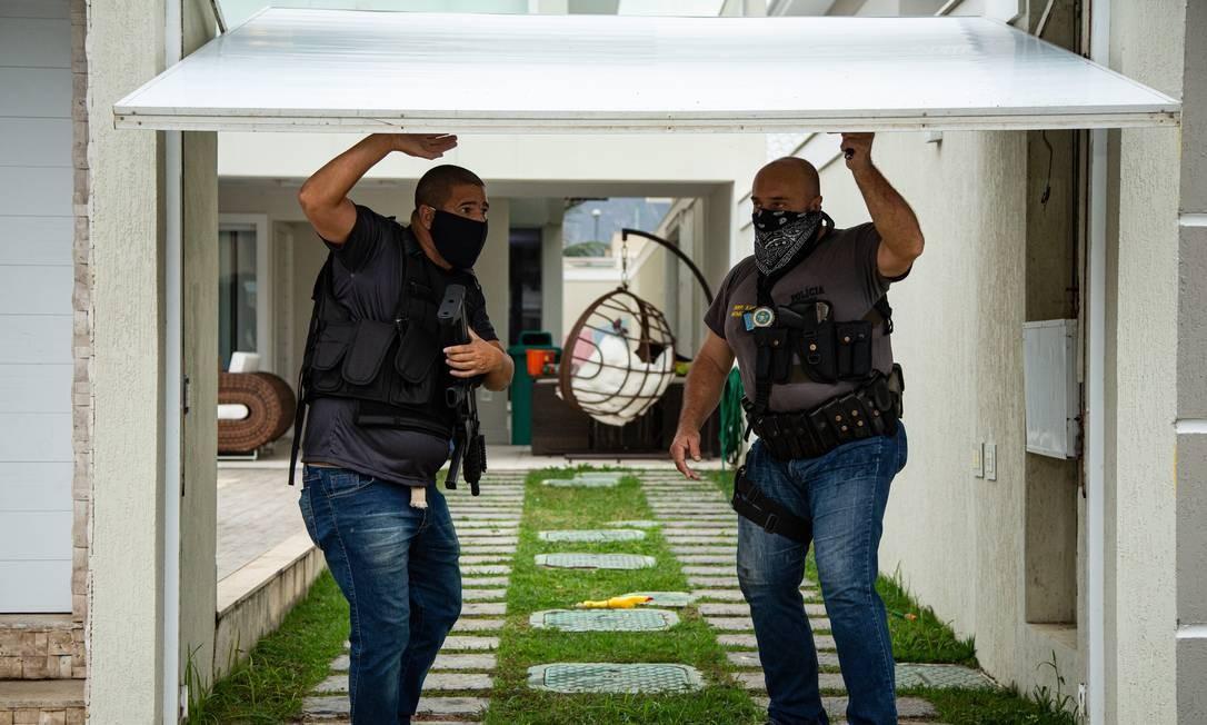 Agentes portão da garagem da casa de Suel para entrada do carro da Polícia Civil Foto: Hermes de Paula / Agência O Globo
