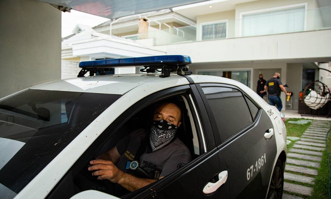 Policial entra na casa de Maxwell com viatura para efetuar a prisão Foto: Hermes de Paula / Agência O Globo