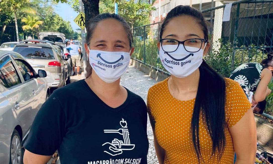 Mariana Assumpção (de blusa mostarda) com uma voluntária do projeto Macarrão com Salsicha contemplada com a máscara divertida Foto: Divulgação