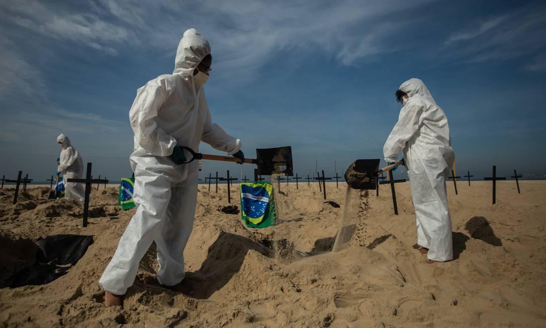 Usando EPI semelhante ao de sepultadores, ativistas cavaram 100 covas rasas na areia de Copacabana Foto: Brenno Carvalho / Agência O Globo