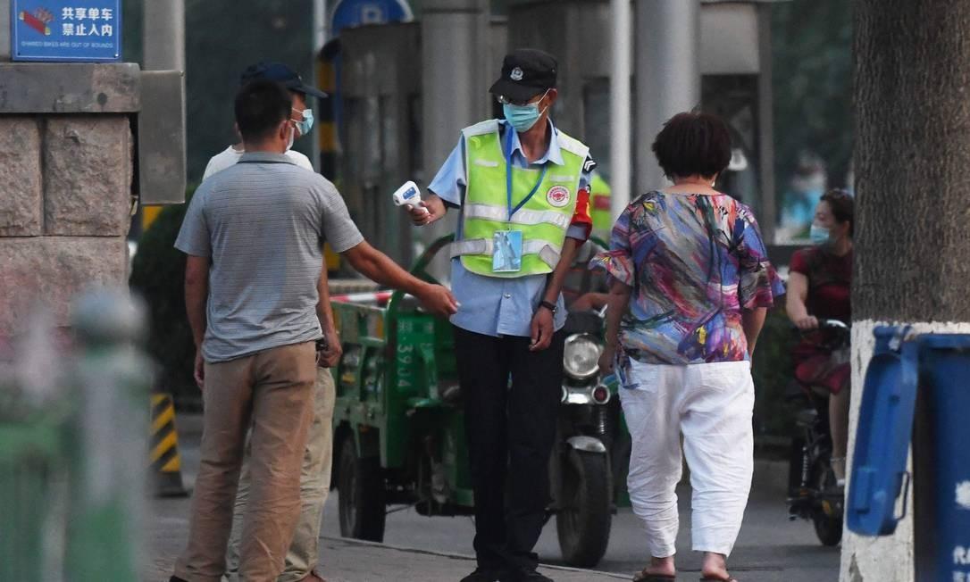 Funcionária mede a temperatura de pessoas em frente ao mercado de Xinfadi, em Pequim, um dos estabelecimentos fechados nesta sexta-feira Foto: GREG BAKER / AFP