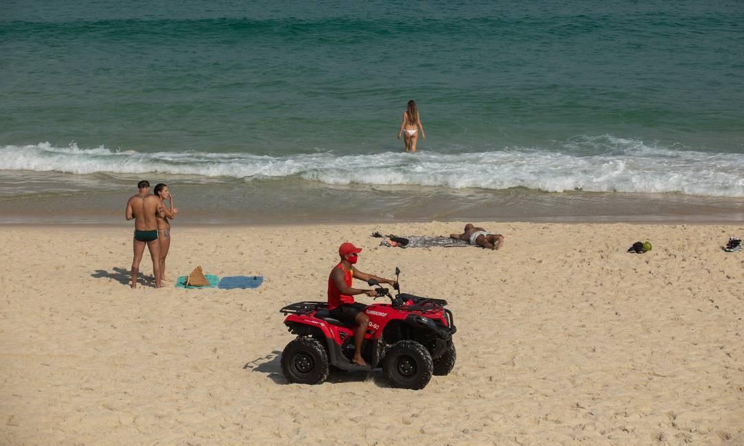 Salva-vida patrulha a Praia da Barra enquanto pessoas tomam banho de mar, o que está proibido pelos decretos do estado e do município Foto: BRENNO CARVALHO / Agência O Globo