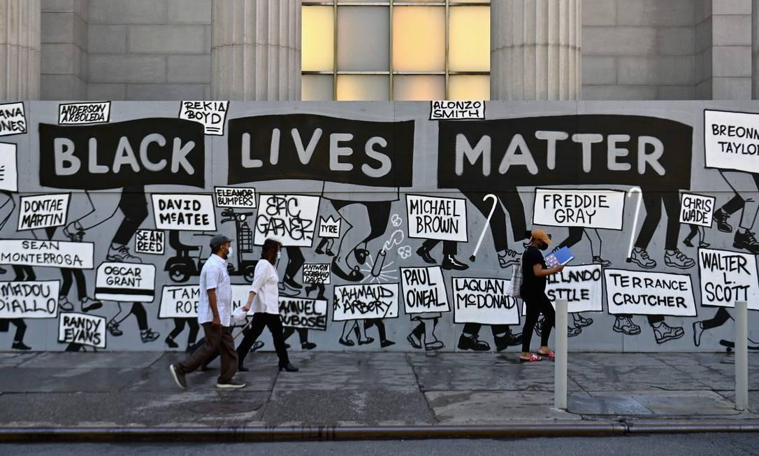 """Pessoas passam por mural com os dizeres """"Black Lives Matter"""" em Nova York Foto: ANGELA WEISS / AFP"""