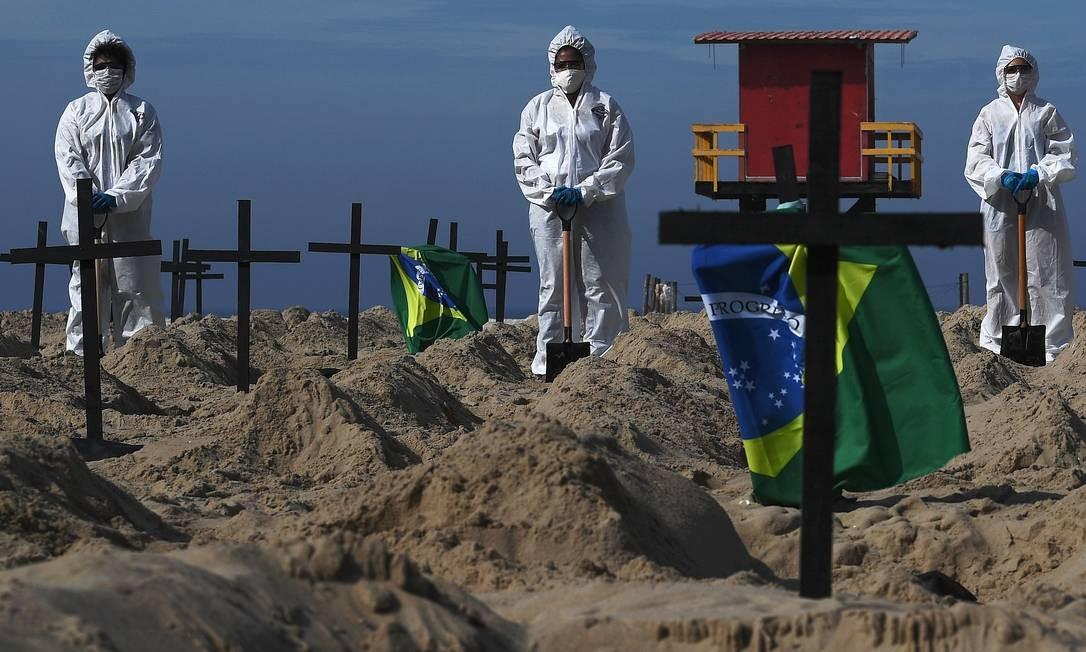 Ativistas da ONG Rio de Paz posam ao lado de cem buracos na areia da Praia de Copacabana, simbolizando sepulturas das vítimas da Covid-19 Foto: CARL DE SOUZA/AFP/11-6-2020