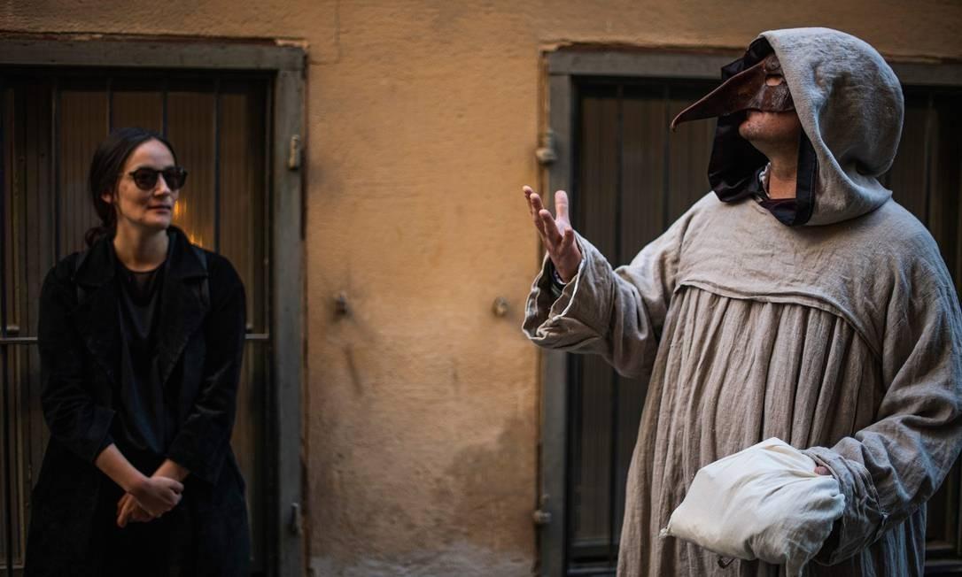 Túnica com capuz e máscara com bico longo compõe a indumentária medieval do guia Mike Anderson durante o passeio guiado sobre epidemias do passado em Estocolmo Foto: JONATHAN NACKSTRAND / AFP