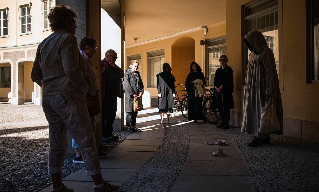 O guia e seu grupo no centro histórico de Estocolmo, durante a Plague Walk Foto: JONATHAN NACKSTRAND / AFP