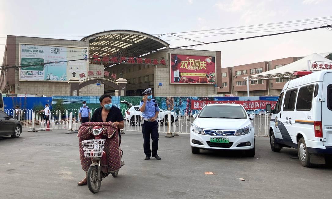 Policiais do lado de fora do mercado Xinfadi, que seria o epicentro de novos casos do novo coronavírus, em Pequim Foto: MARTIN POLLARD / REUTERS