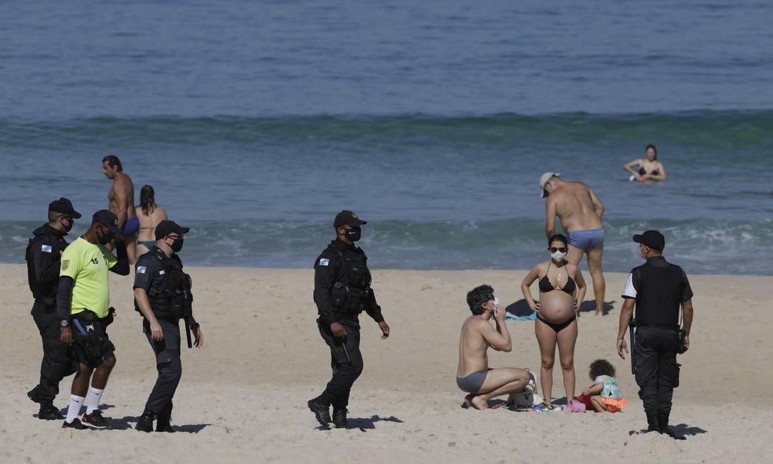 Policiais tentavam impedir que banhistas ficassem parados nas areias da Zona Sul Foto: Gabriel de Paiva