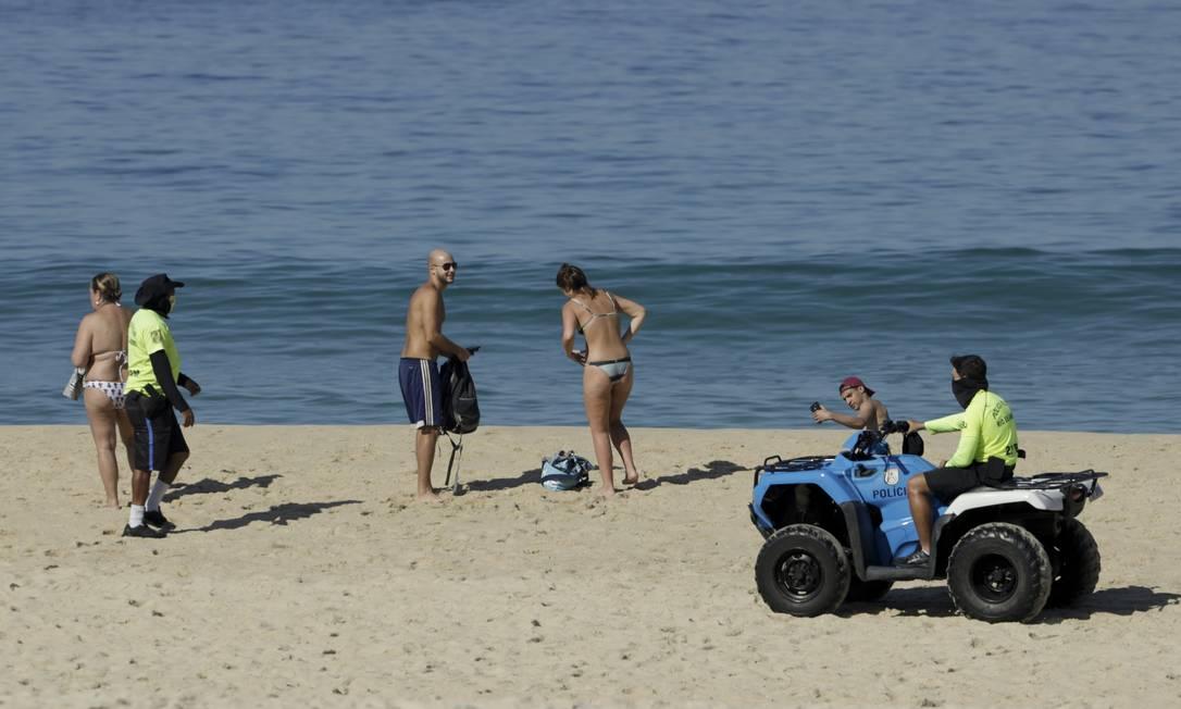 Apesar dos pedidos dos policiais militares, banhistas não arredam pé da areia da praia em Ipanema Foto: Gabriel de Paiva/13-6-2020 / Agência O Globo