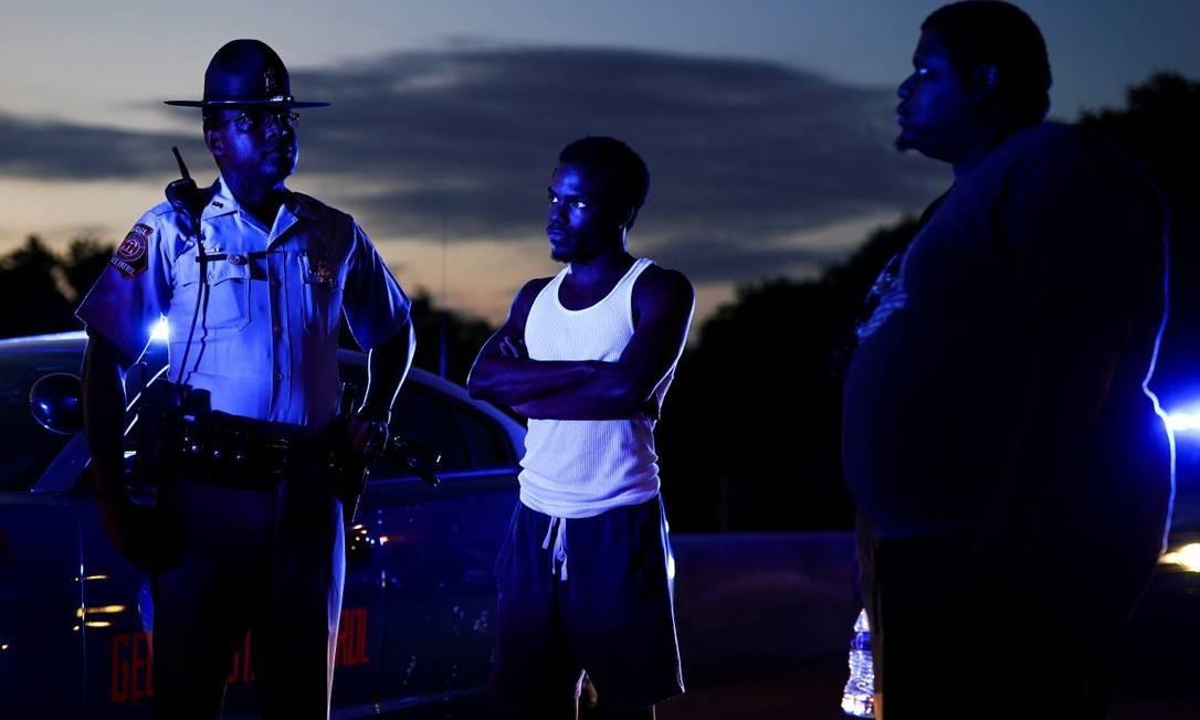 Dois manifestantes conversam com um policial após bloquearem uma rodovia durante uma manifestação contra a desigualdade racial e a morte de Rayshard Brooks, em Atlanta, na Geórgia Foto: ELIJAH NOUVELAGE / REUTERS