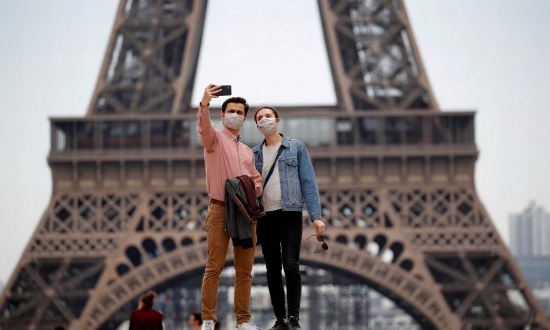 Em Paris, casal de máscaras tira foto em frente à Torre Eiffel Foto: Gonzalo Fuentes / REUTERS / 16-5-2020