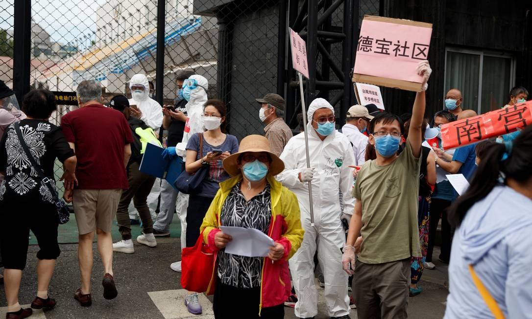 Pessoas se aglomeram na entrada de centro esportivo para serem testadas após um inesperado novo foco de contaminações por coronavírus em Pequim Foto: THOMAS PETER / REUTERS/15-06-2020