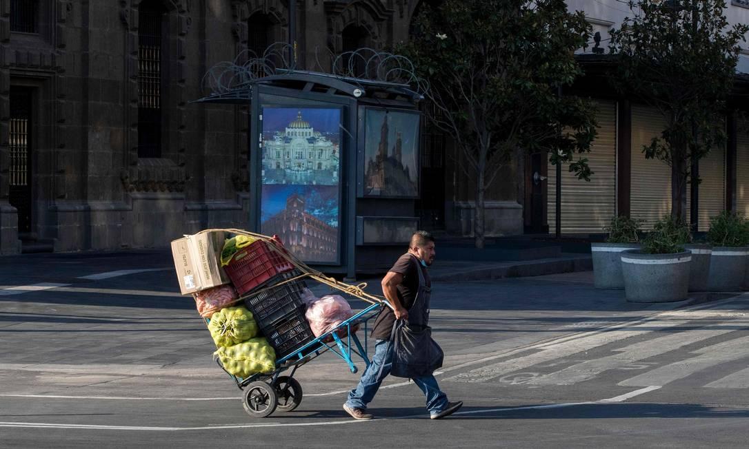 Vendedor puxa carrinho com frutas e legumes no Centro Histórico da Cidade do México em meio à pandemia de coronavírus Foto: CLAUDIO CRUZ / AFP/14-06-2020