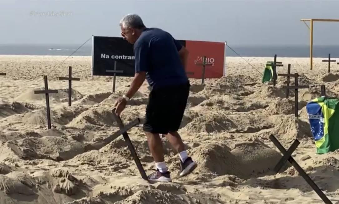 Héquel Osório derruba uma das cruzes colocadas pela ONG Rio de Paz na Praia de Copacabana Foto: Reprodução de vídeo