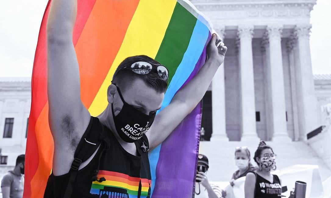 Um homem segura a bandeira do arco-íris em frente à Suprema Corte dos EUA que decidiu que a lei federal americana protege trabalhadores LGBTQ+ da discriminação Foto: JIM WATSON / AFP