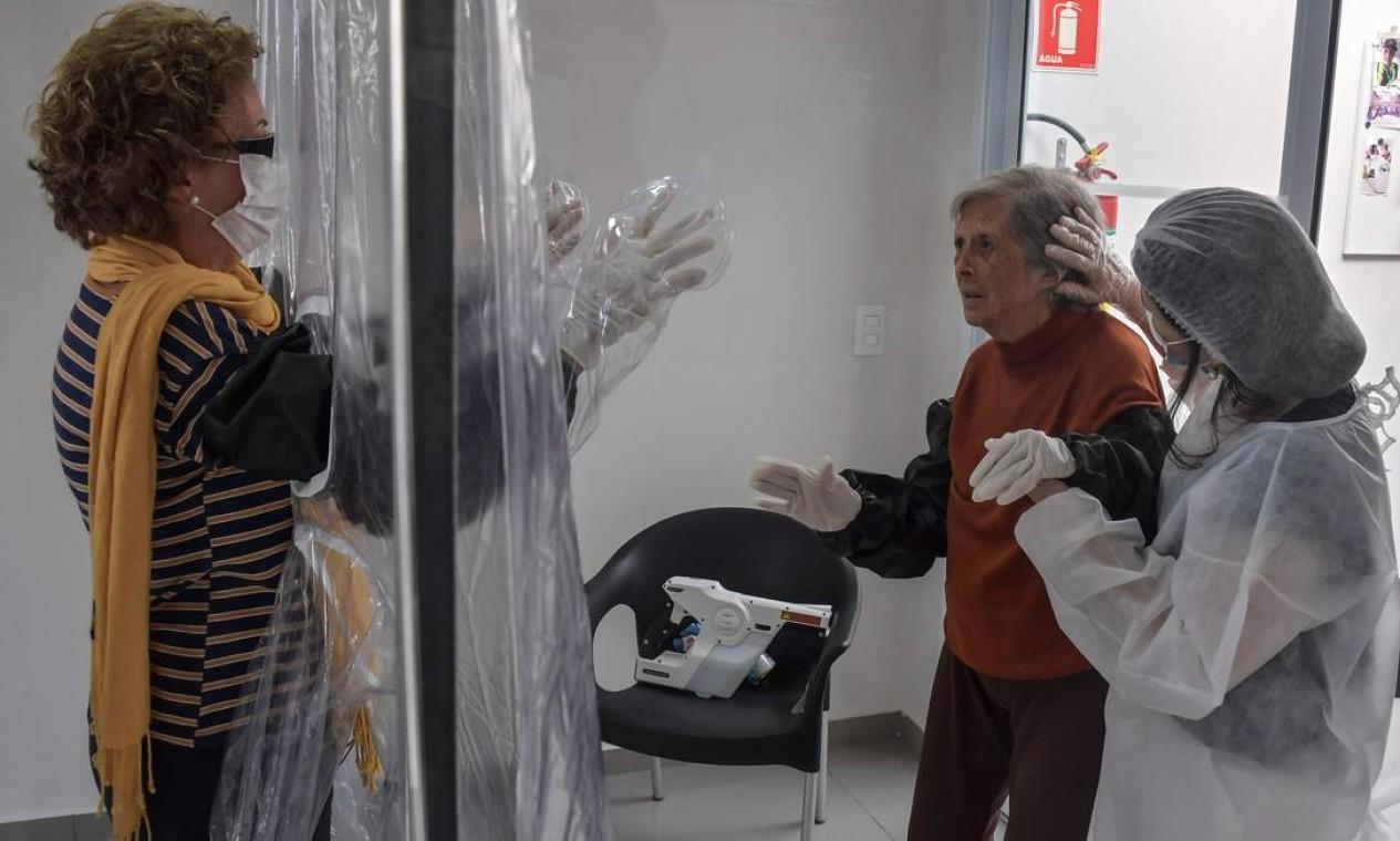 Dircyree Villas Boas acena para sua mãe, Dirce Villas Boas, de 93 anos, através da cortina de proteção. A ideia veio de uma experiência realizada nos Estados Unidos Foto: NELSON ALMEIDA / AFP