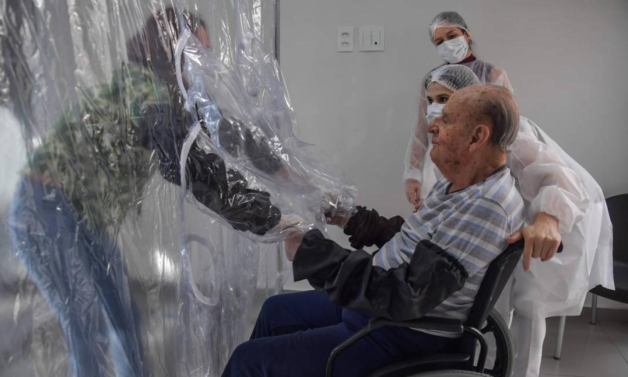 Suzane Lisboa segura as mãos do seu pai, Raul Lisboa, de 89 anos. Os grandes bolsos permitem que visitantes e residentes possam, finalmente, romper, pelo menos em parte, o distanciamento Foto: NELSON ALMEIDA / AFP