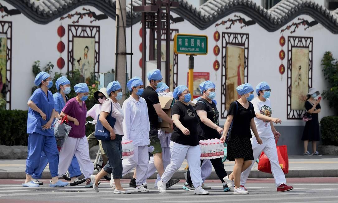 Trabalhadores da saúde a caminho de uma instalação médica para realizar testes em pessoas que estiveram no mercado de Xinfadi, onde surgiu o novo surto do novo coronavírus em Pequim Foto: Noel Celis / AFP