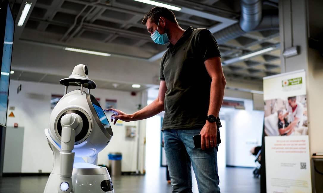 Funcionário da empresa belga ZoraBots testa um robô chamado Cruzr, Hospital Universitário da Antuérpia. Este robô está configurado para rastrear as temperaturas dos visitantes do hospital e detectar se eles estão usando máscaras Foto: KENZO TRIBOUILLARD / AFP