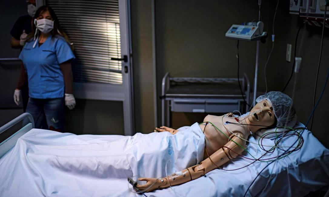 Médica Norma Raul olha um robô com o qual ela pratica assistência médica para pacientes com Covid-19, no Centro de Treinamento em Simulação Clínica do hospital El Cruce, em Florencio Varela, Província de Buenos Aires, Argentina Foto: RONALDO SCHEMIDT / AFP