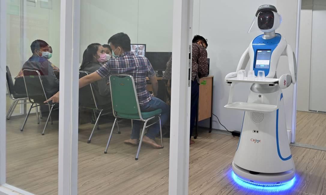 Robô conhecido como Amy passa por teste de bandeja, com copos de água selados durante uma simulação para ajudar as equipes médicas a lidar com pacientes com coronavírus, no hospital Pertamina Jaya em Jacarta Foto: ADEK BERRY / AFP