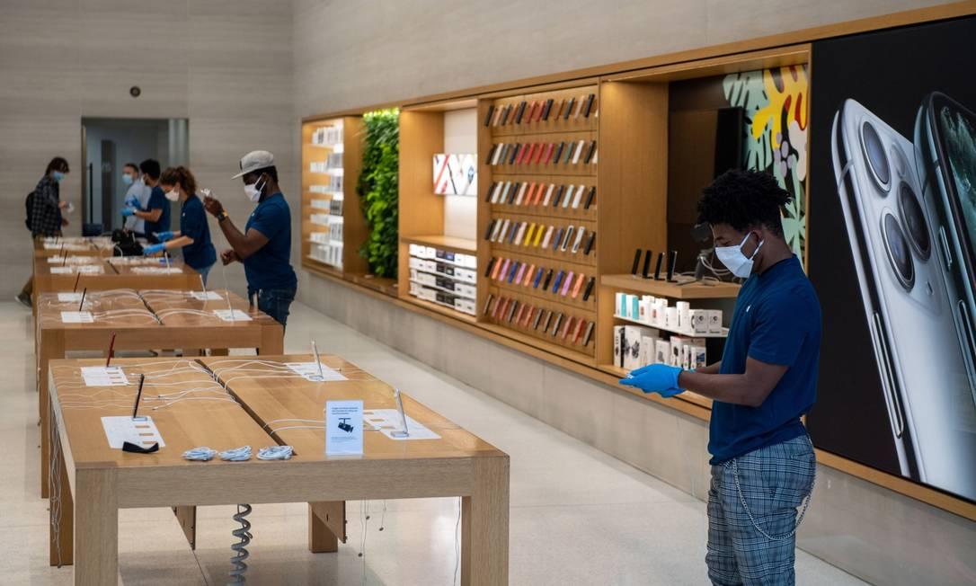 Funcionários usam máscaras de proteção em loja da Apple em Londres Foto: Chris J. Ratcliffe / Bloomberg