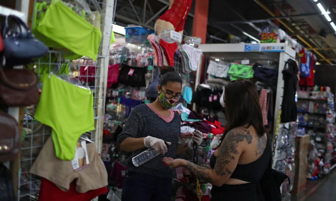 Funcionária de uma loja aplica álcool em gel nas mãos de uma cliente no Mercadão de Madureira, que reabriu nesta terça-feira, seguindo cronograma da segunda fase do plano de flexbilização no Rio Foto: PILAR OLIVARES / REUTERS
