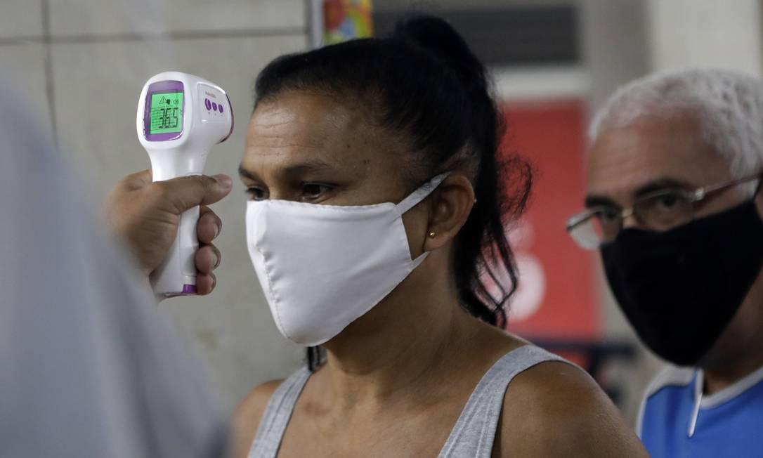 Protocolo: cliente tem a temperatura medida antes de entrar no Mercadão de Madureira, reaberto nesta quarta-feira Foto: Luiza Moraes / Agência O Globo