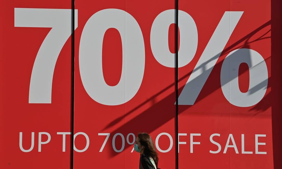 REINO UNIDO - Uma mulher passa por uma vitrine com anúncio de desconto do lado de fora de uma loja na Oxford Street, em Londres. Várias lojas e atrações ao ar livre abriram pela primeira vez em quase três meses Foto: JUSTIN TALLIS / AFP