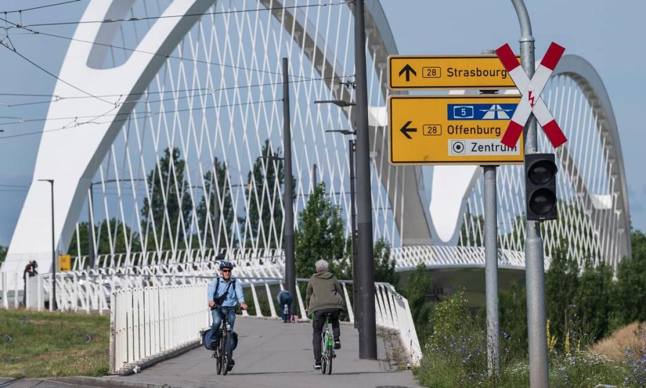FRANÇA / ALEMANHA - Ciclistas atravessam a ponte que liga Estrasburgo, na França, e Kehl, na Alemanha, após reabertura das fronteiras, em 15 de junho Foto: PATRICK HERTZOG / AFP