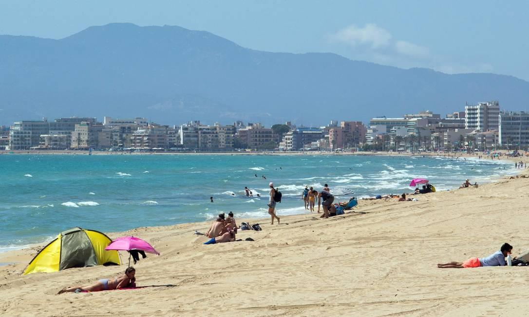 ESPANHA - Banhistas aproveitam o sol na praia de Palma, em Palma de Maiorca, em 15 de junho. As Ilhas Baleares recebem turistas alemães, que participam de um teste de planos para reabrir o destino popular à medida que a Espanha emerge de seu confinamento Foto: JAIME REINA / AFP