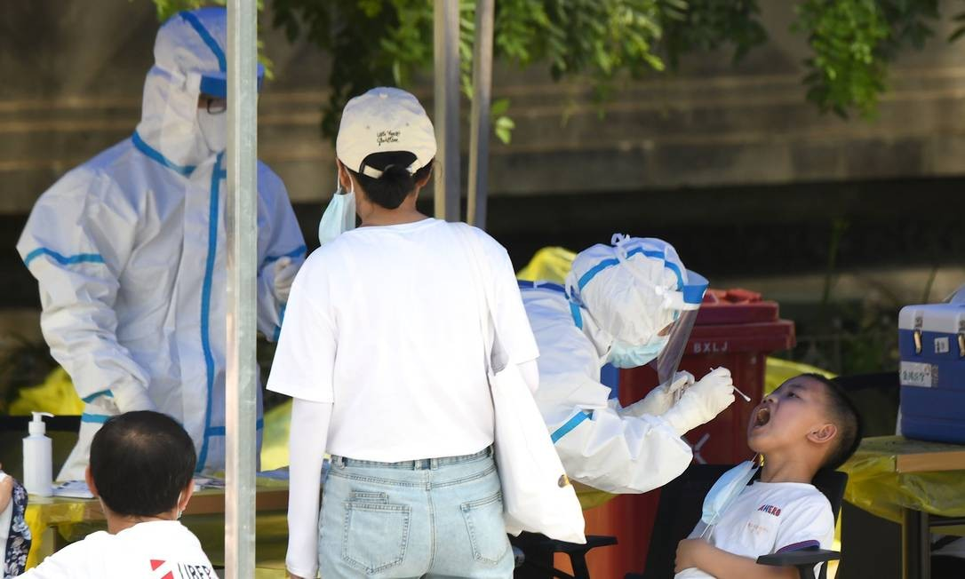 CHINA - Agente de saúde realiza teste em um menino, em Pequim, em 16 de junho. A China relatou outros 27 casos de coronavírus transmitidos domesticamente em Pequim, onde um novo surto, com mais de cem casos, vinculado a um mercado atacadista de alimentos despertou a preocupação da OMS e levou a um enorme programa de rastreamento e teste Foto: NOEL CELIS / AFP