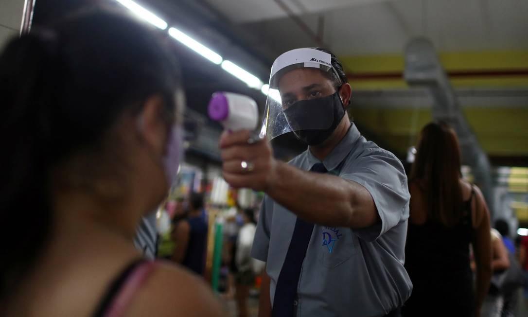 Mulher tem temperatura medida ao entrar no Mercadão de Madureira, no Rio. Foto: PILAR OLIVARES / REUTERS