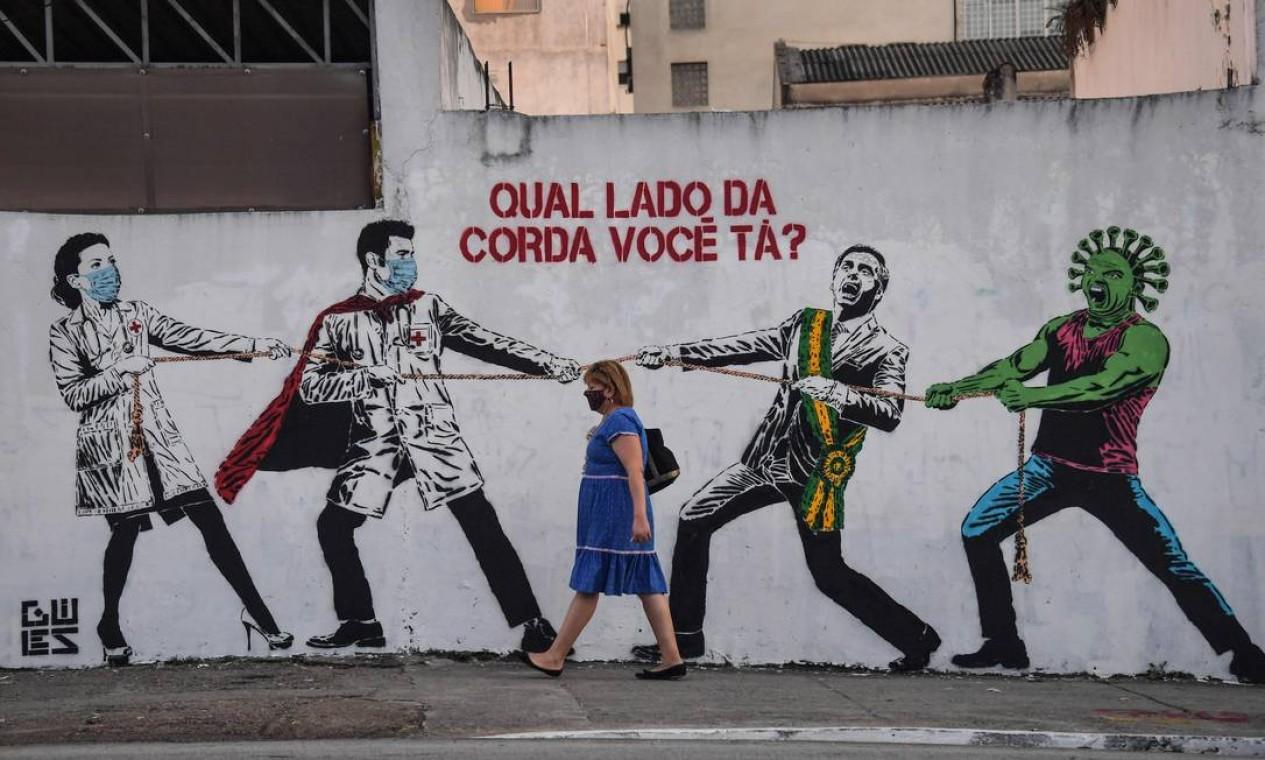 BRASIL - Um grafite mostra o presidente Jair Bolsonaro e o coronavírus contra profissionais de saúde, em 12 de junho. Brasil é o segundo país com mais mortes no mundo (mais de 44 mil), ficando atrás apenas dos EUA, que soma mais de 116 mil vidas perdidas para a Covid-19 Foto: NELSON ALMEIDA / AFP