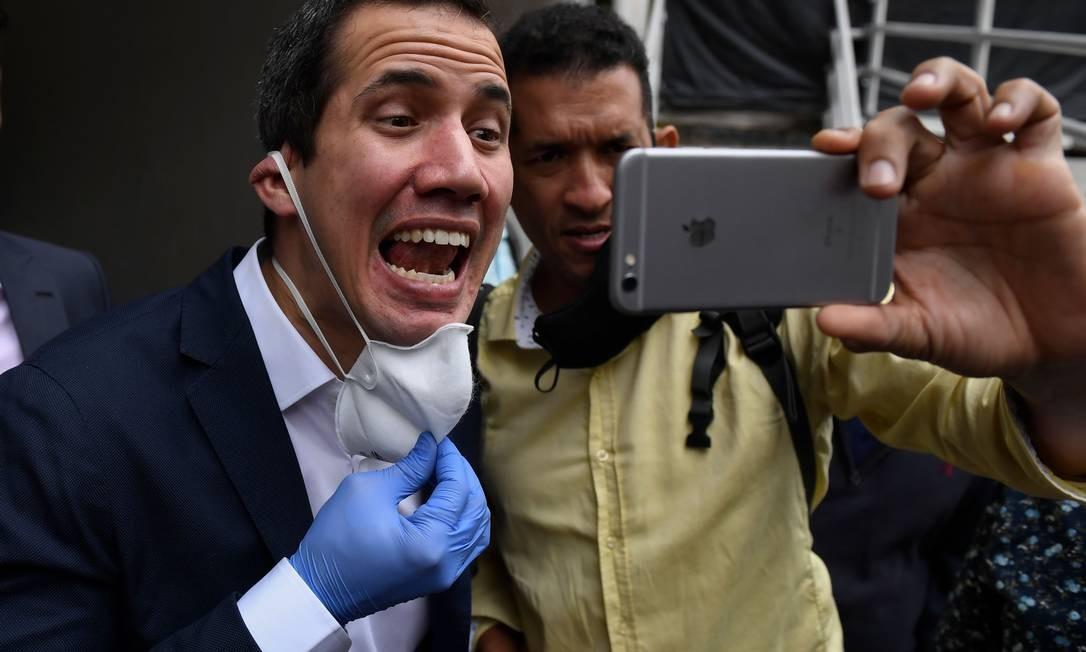 Juan Guaidó, reconhecido como presidente interino da Venezuela por mais de 50 países, posa sem máscara para foto com apoiador em Caracas: oposição enfraquecida Foto: FEDERICO PARRA / AFP