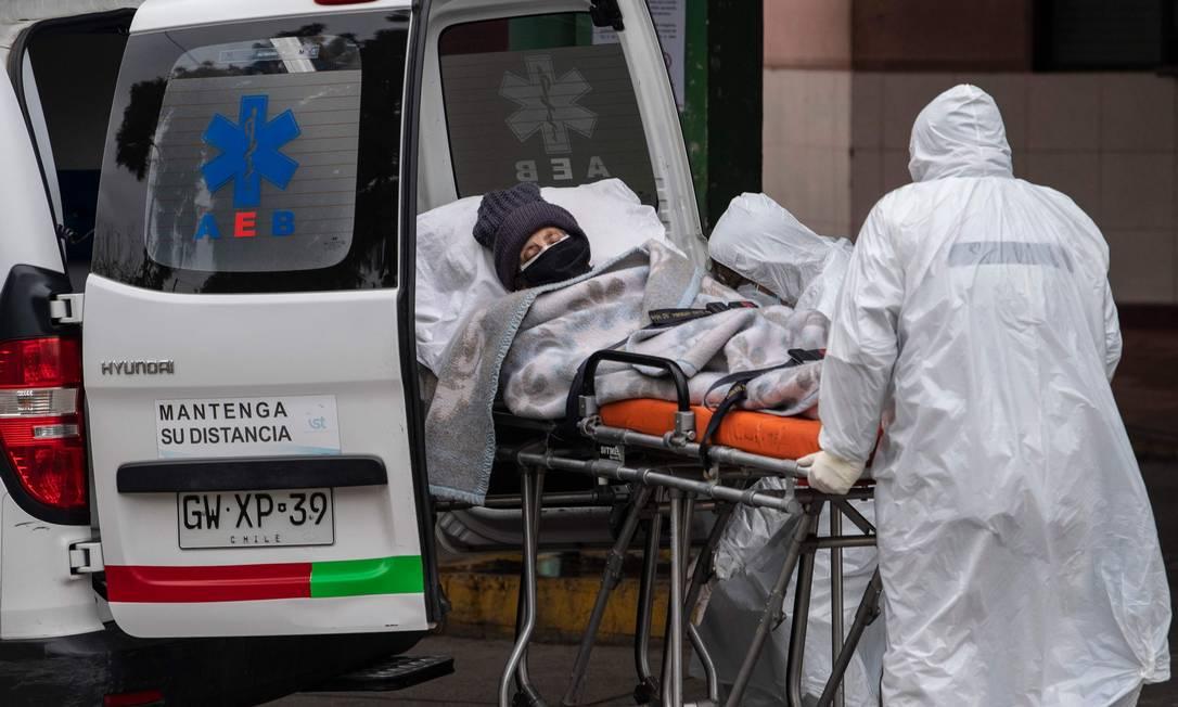 Equipe de saúde transfere paciente com sintomas do novo coronavírus após ser internado no Hospital San Jose, em Santiago, no Chile Foto: MARTIN BERNETTI / AFP/18-06-2020